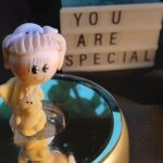 "Clay figure with a sign saying ""you are special"" in the background"