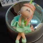 "A clay figure sitting with the word ""special"" in the background"