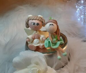 Two clay figures sitting together with a feather background