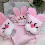 Three pink cloth rabbits with pearl eyes