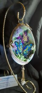 A hollow egg held up with a golden hook with curvature, with a elaborate scene featuring a butterfly within.
