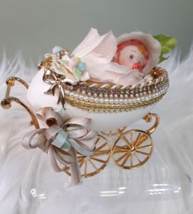 An egg hollowed out with wheels resembling a carriage with a baby inside.