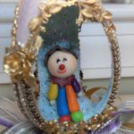 Jeweled egg with an open, glittered interior with a clown doll inside.