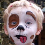 Blonde child with white, black, and brown face paint resembling a dog.