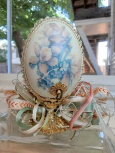 Gallary egg with pearl and jewel outline, sitting atop a golden base with ribbon.