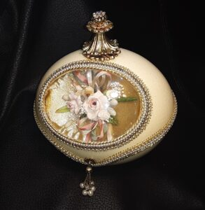 Goose egg with gold top, jeweled necklace, with a flowery image in the middle.