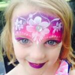 A little girl with face paint around the forehead with flowers and stems.