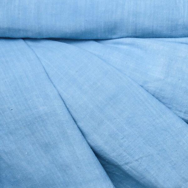 Image of a roll of sky blue organic handspun cotton fabric draped