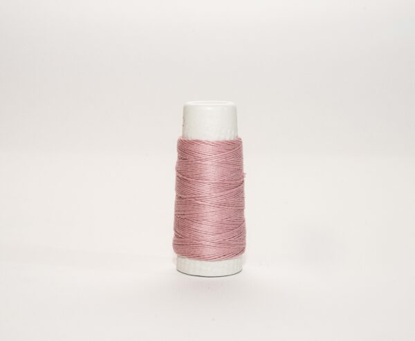 an image of a pink spool of thread