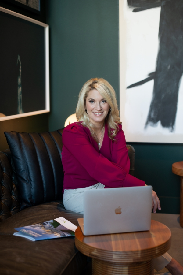 nancy sitting behind laptop smiling