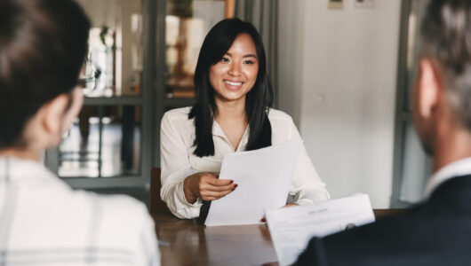 Business, career and recruitment concept - young asian woman smiling and holding resume while interviewing as candidate for job in big company