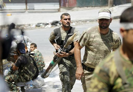 A Free Syrian Army fighter carries an RPG during clashes in Aleppo