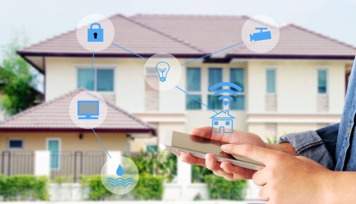 Hand using smart phone as smart home control application over blurred house background, smart home concept
