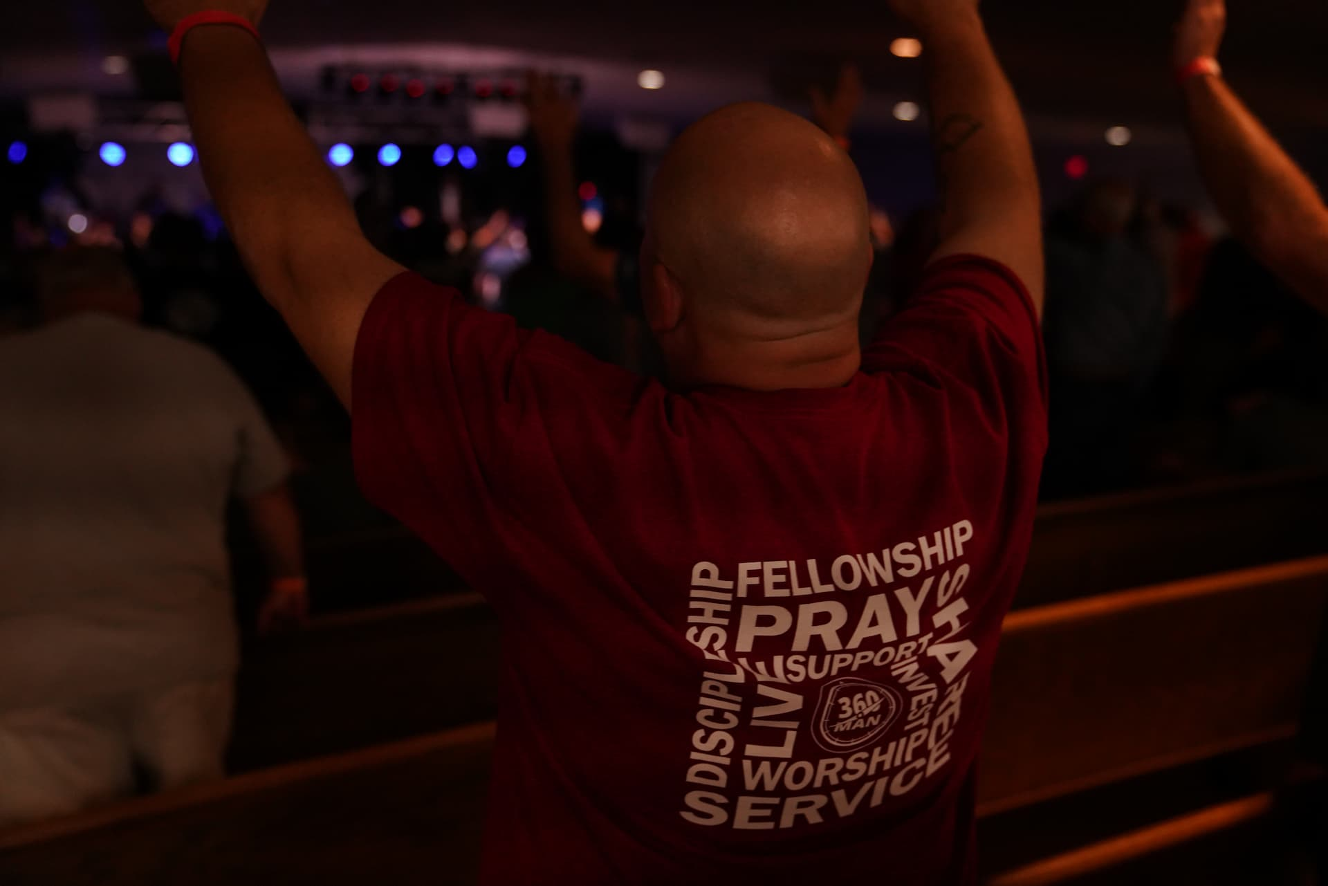360 Man in red shirt with arms raised worshipping God