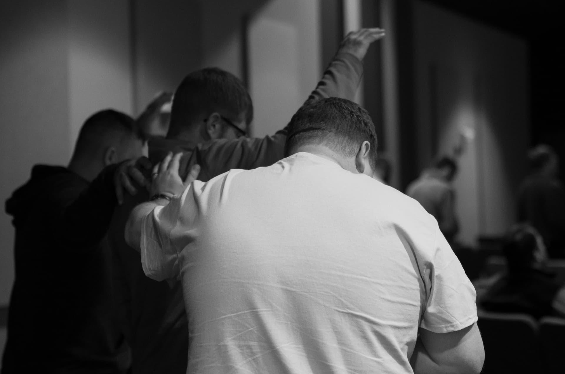 Men praying for each other while worshipping Jesus