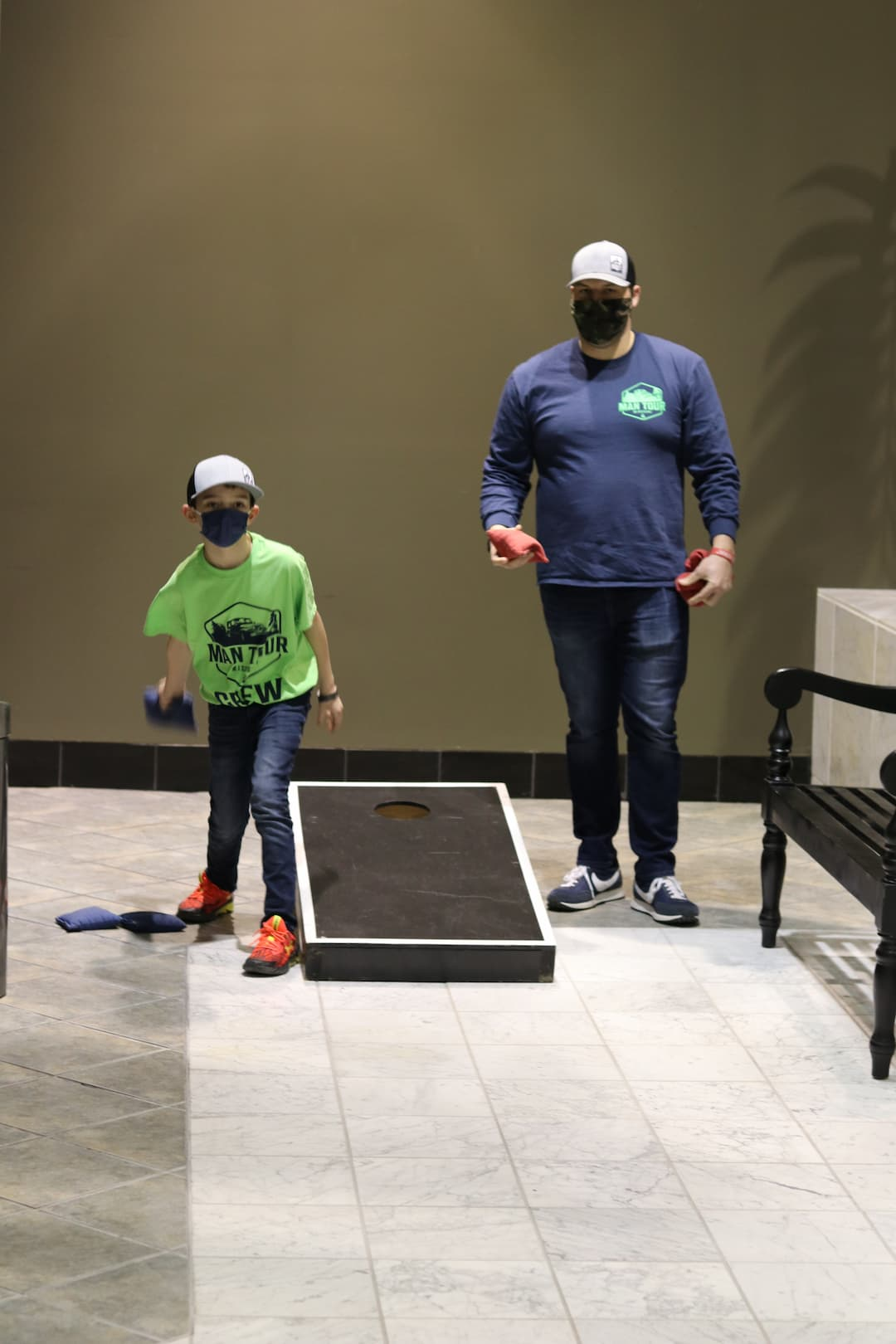 Father son playing cornhole at men's ministries event