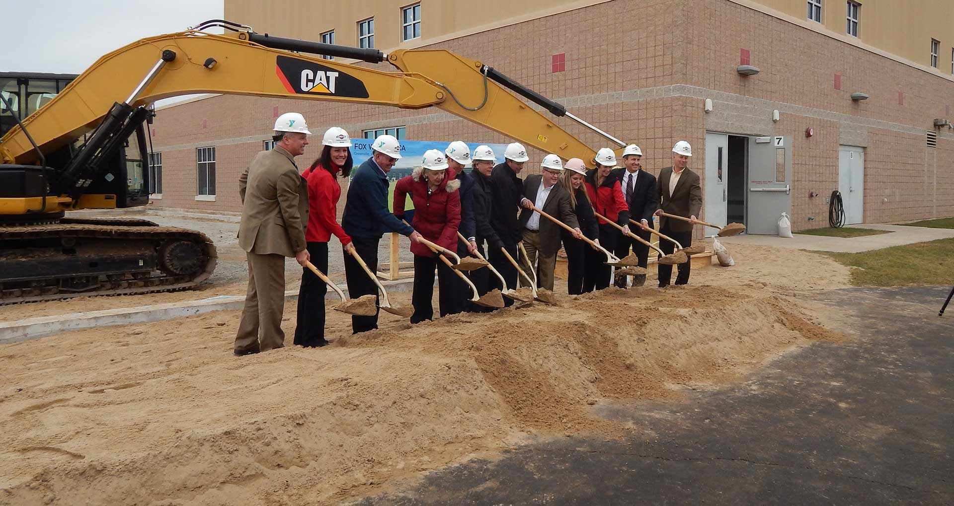 Group of people with shovels at ground breaking ceremony.