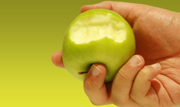 hand holding a bitten green apple