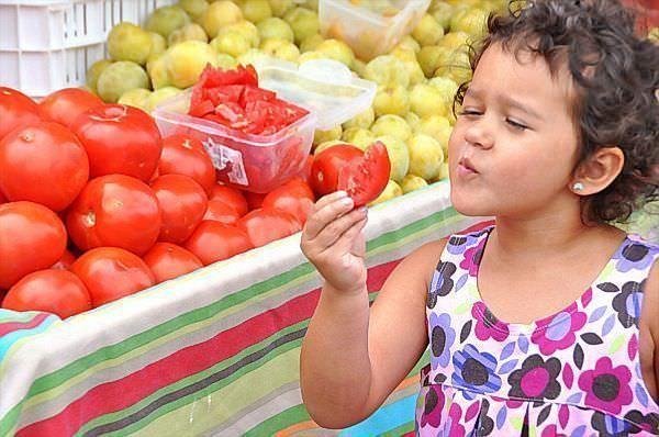 girl tasting tomato via richandkathy.com