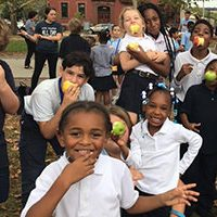 Kids of Allegheny Traditional Academy eat apples at the North Side farmers market, Oct. 2017