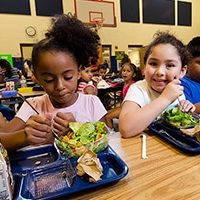 elementary school children eat lunch in cafeteria