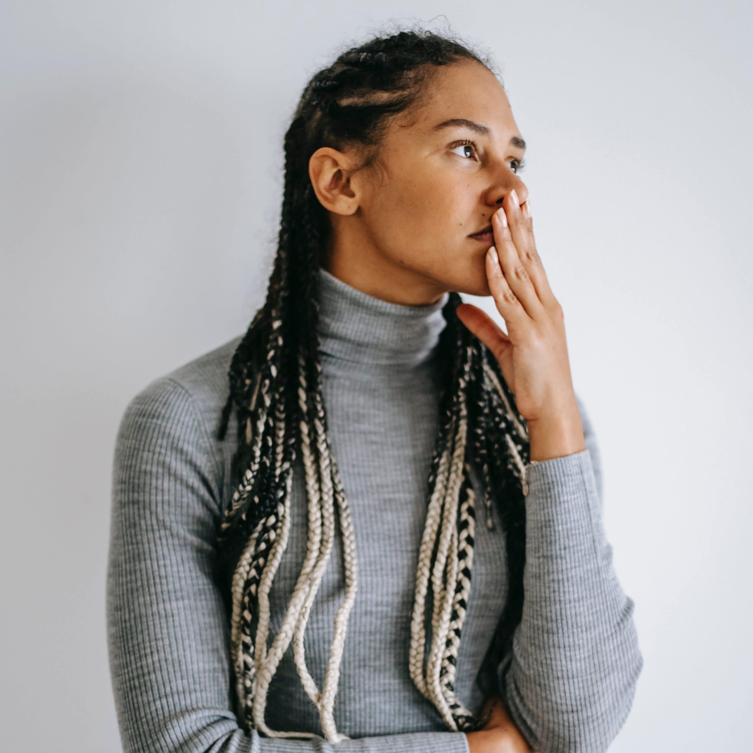 Anxiety can be soothed with sensory based practices. A woman with brown skin and long white-tipped braids anxiously touches her mouth while wearing a gray turtleneck sweater.