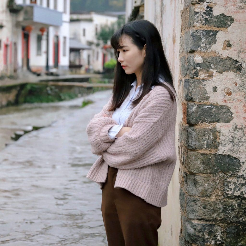 Trauma can stem from a number of experiences. A woman in a pink cardigan leans against a building with crumbling paint.