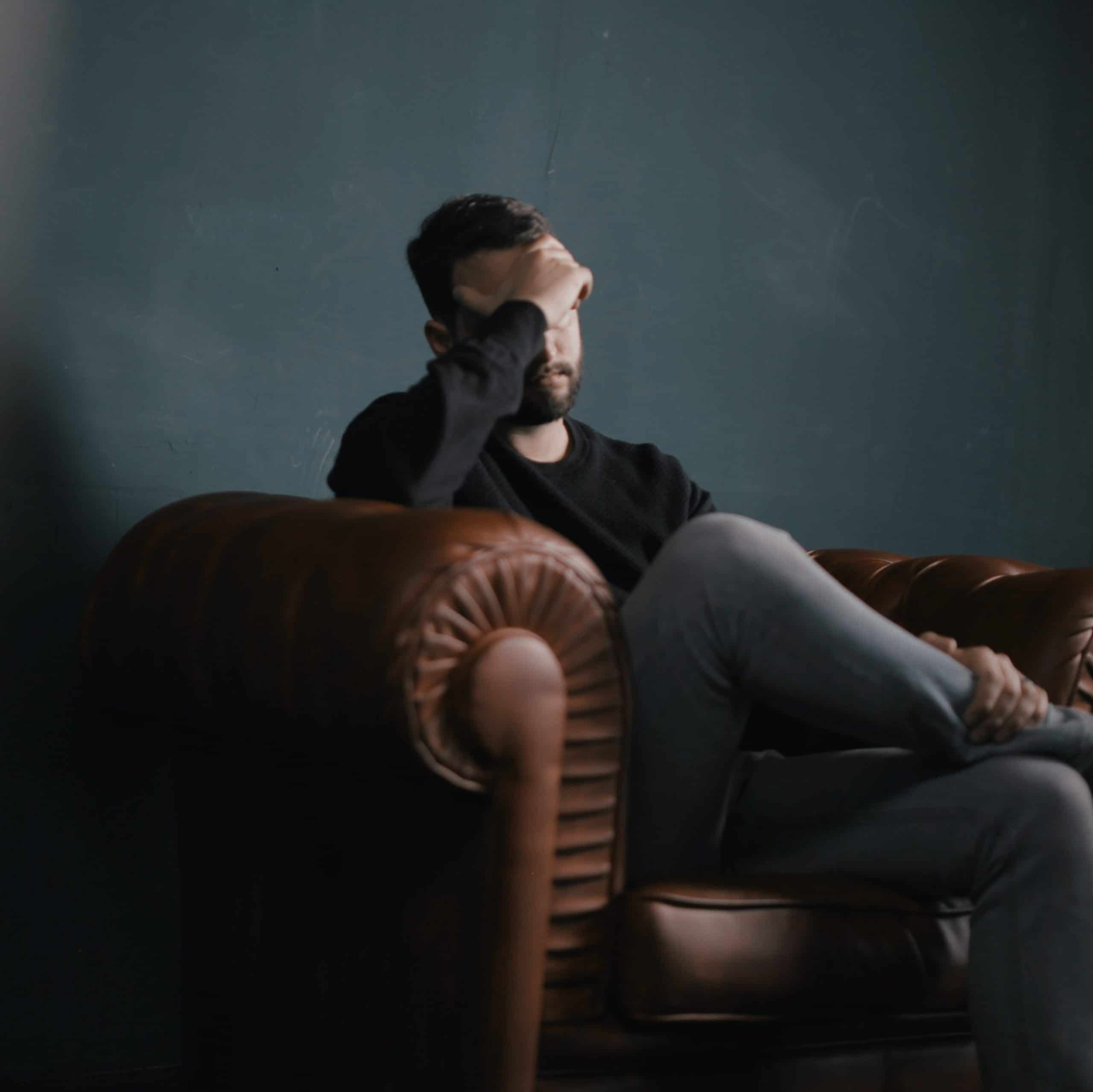 A man sits in a brown leather armchair and massages his temples.