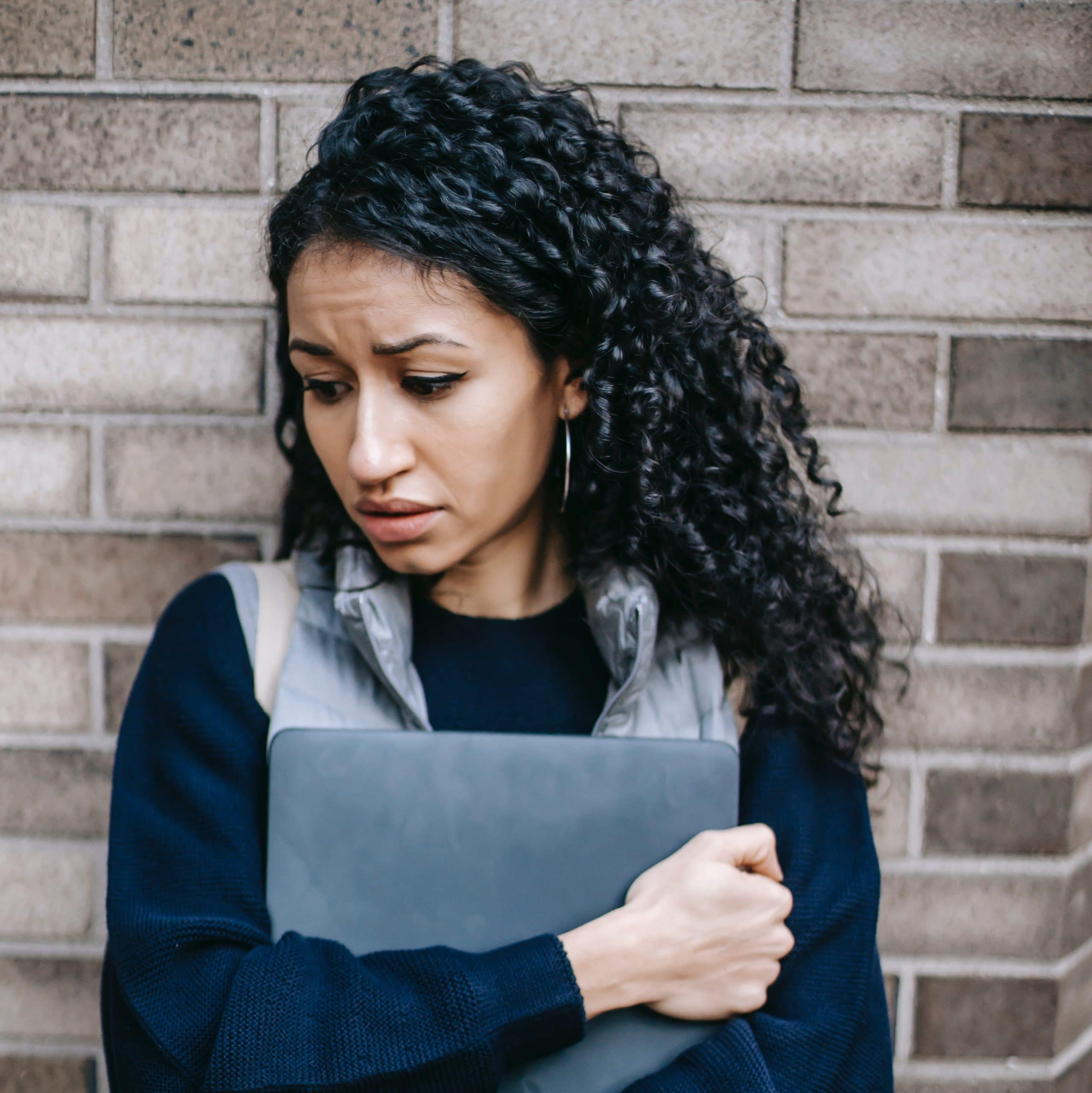 Trauma can affect anyone at any time. A Latina woman leans against a brick wall while holding a laptop and looking anxious.