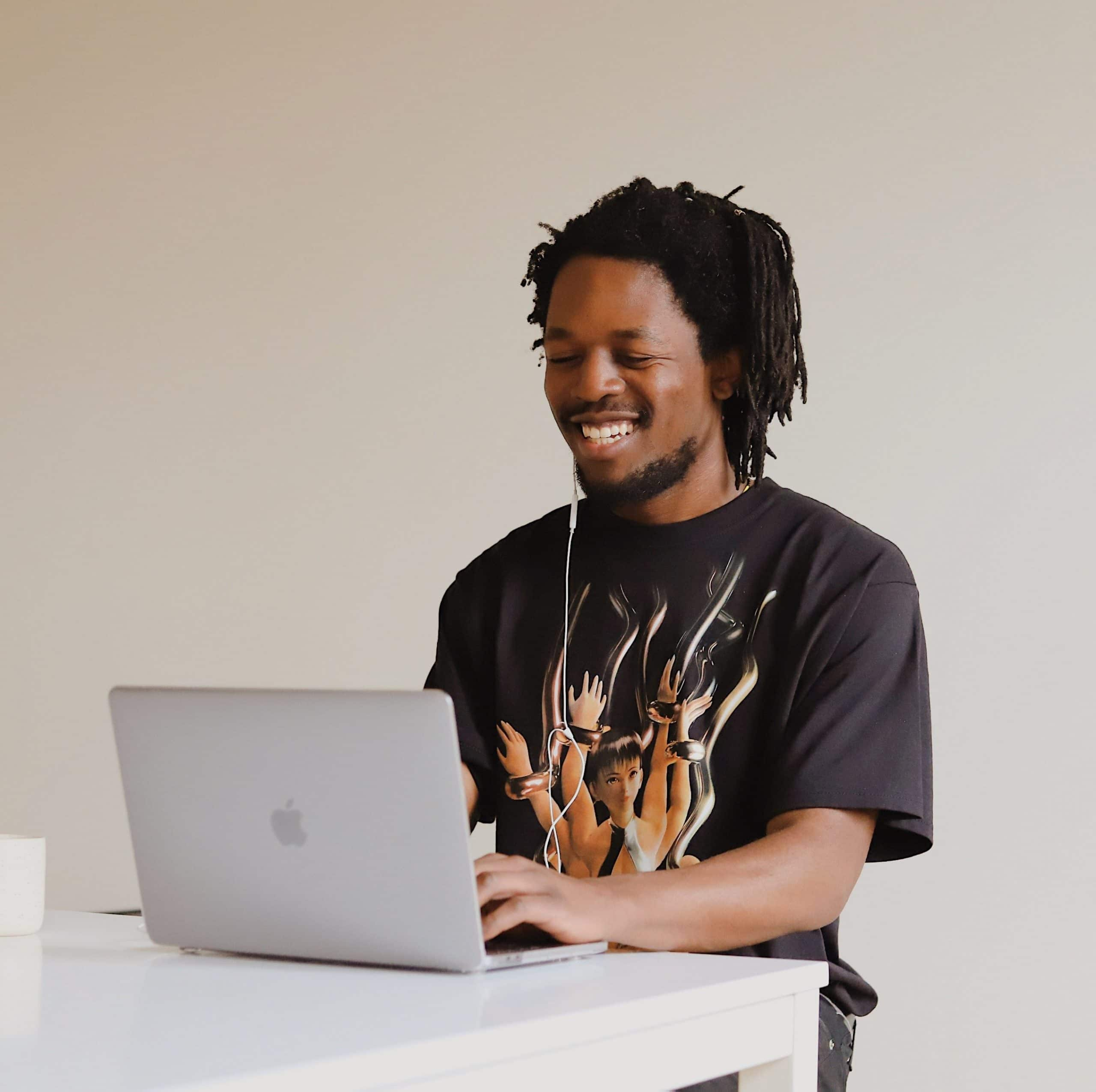 A young man smiles at his laptop during online therapy.