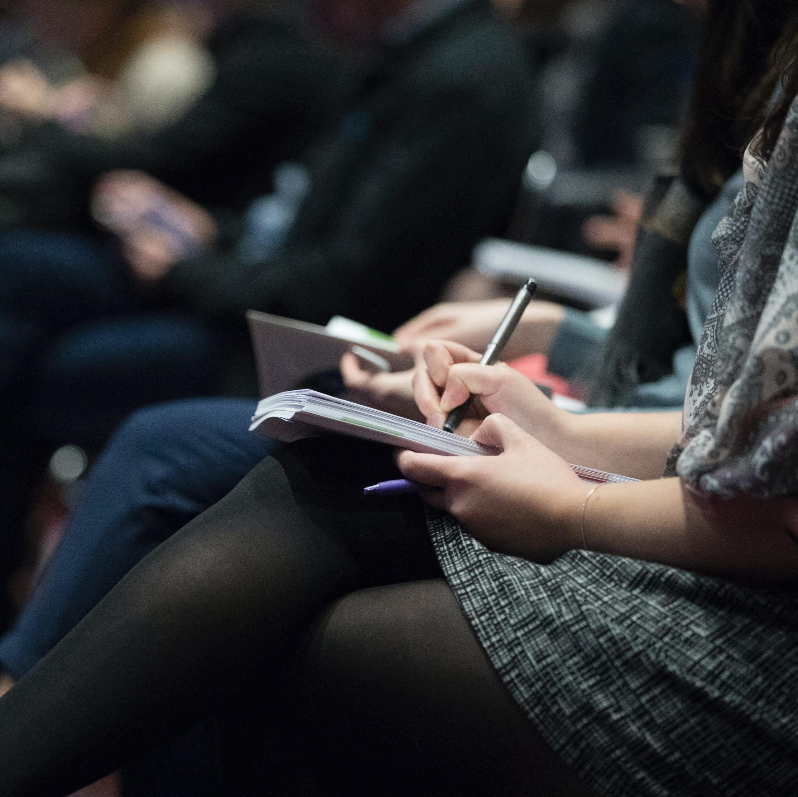 A person in the foreground wearing a skirt and tights takes notes while others in the background listen during a lecture.