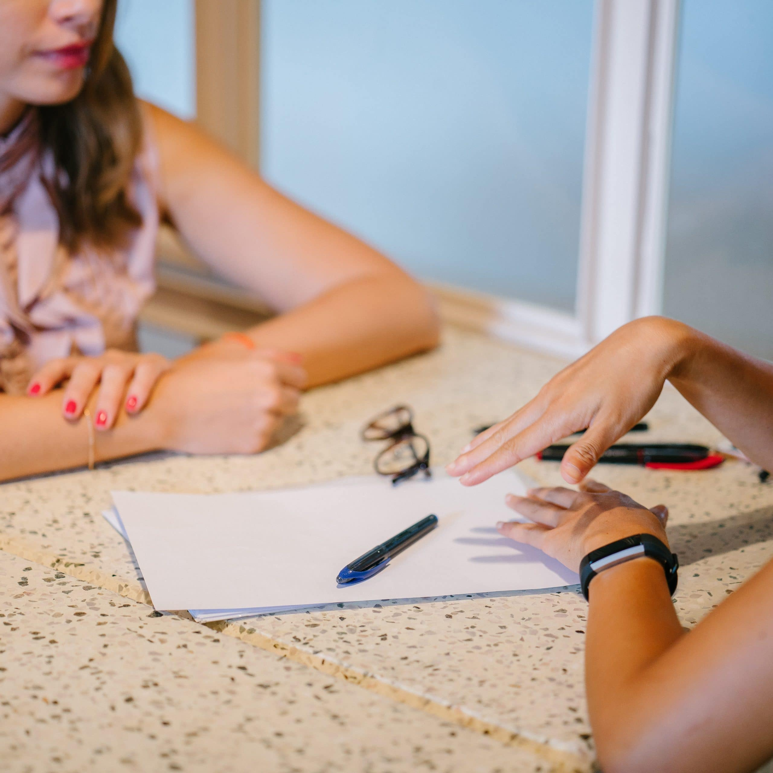 Two women with painted nails sit at a table while having a conversation over psychological evaluation paperwork.