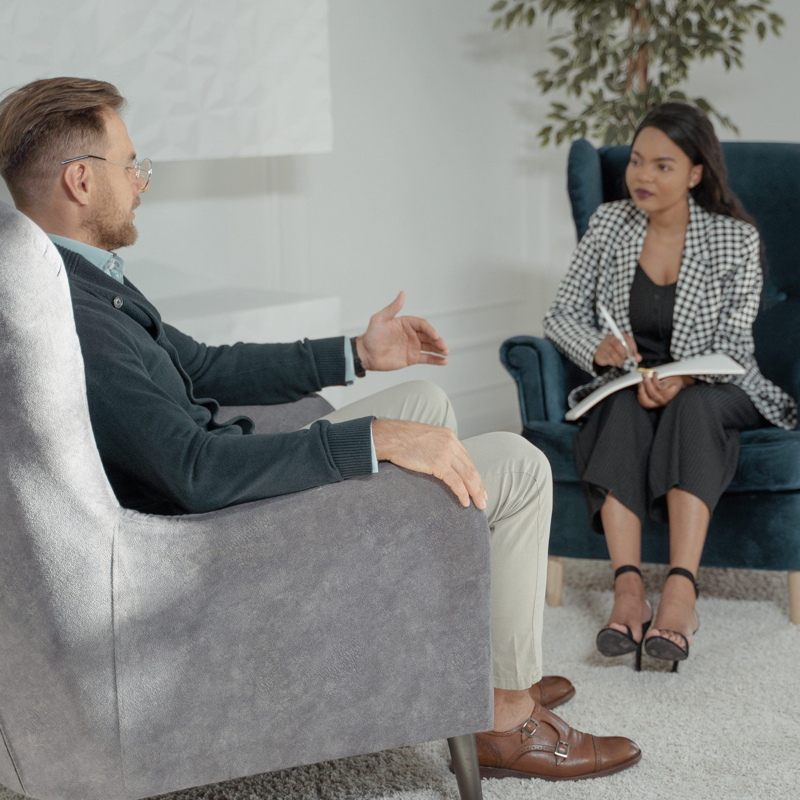 A man and a woman in business clothing sit in wingback chairs and talk.