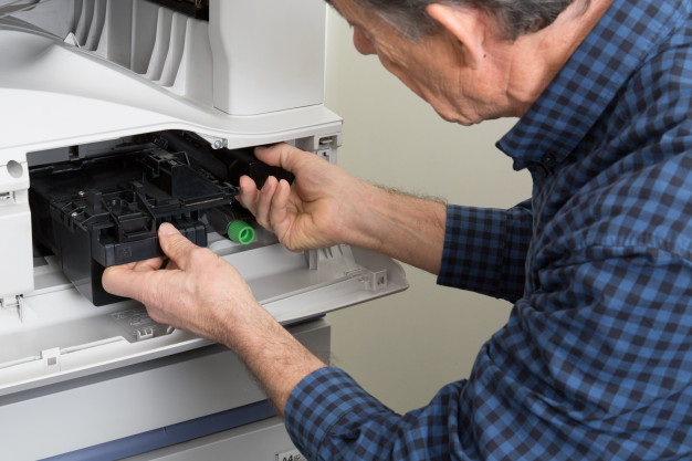 closeup-shot-male-technician-repairing-digital-photocopier-machine_100800-4403