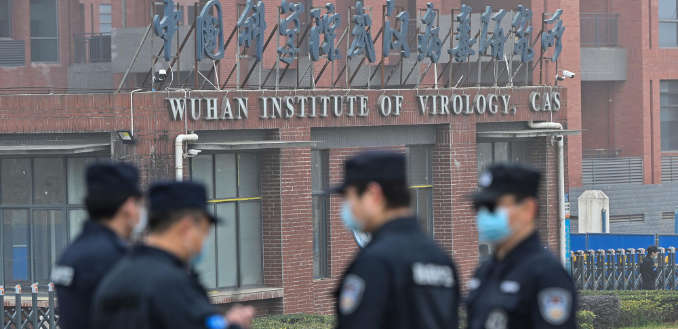 Security personnel stand guard outside the Wuhan Institute of Virology in Wuhan in February, as members of the World Health Organization (WHO) team investigating the origins of the Covid-19 coronavirus pay a visit.