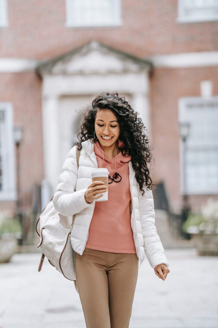 woman walking alone looking at her phone with headphones around her neck