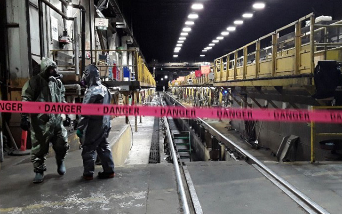 workers in hazmat suits walk a around quarantined facility