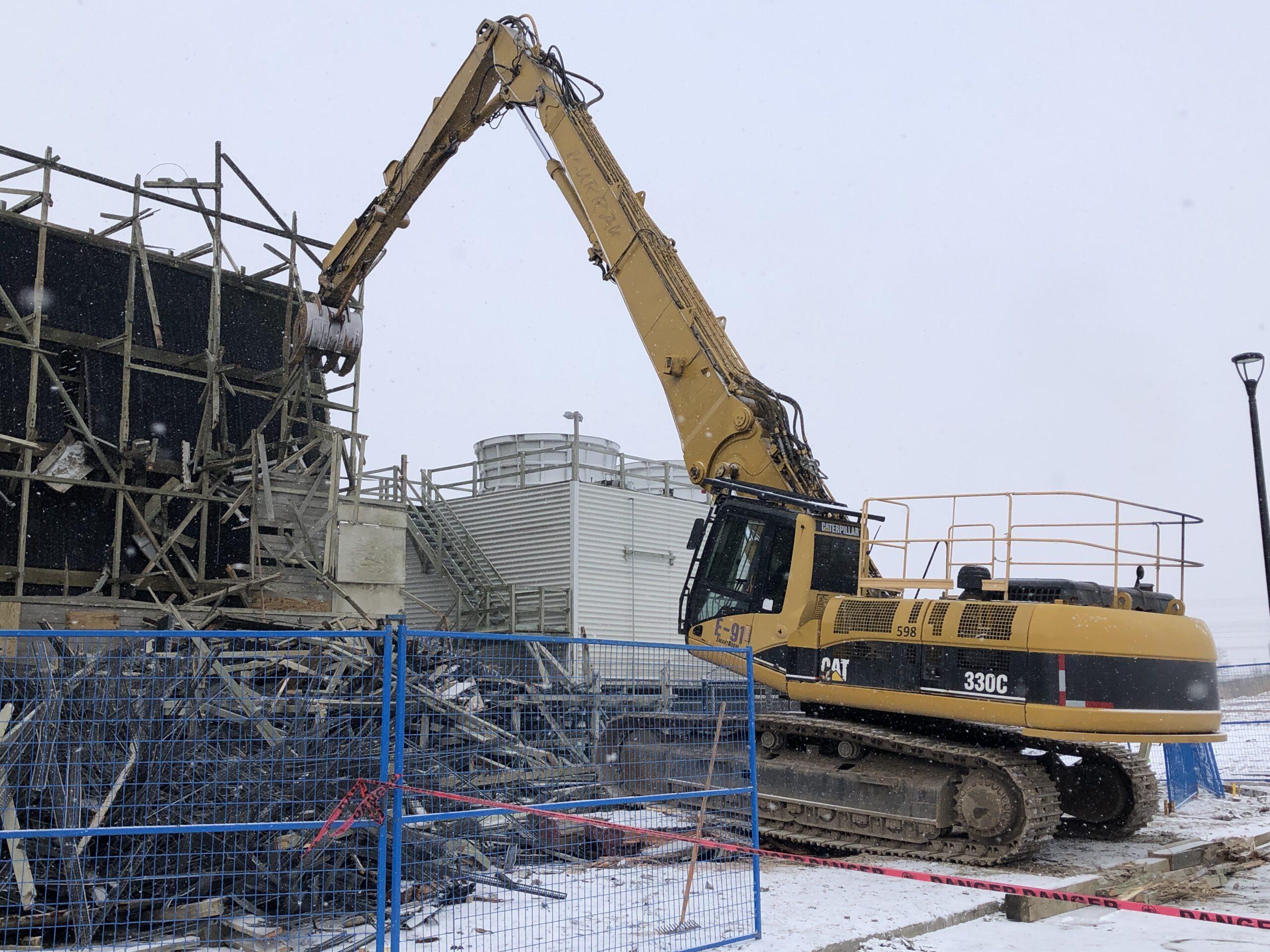 Excavator demolishing the cooling tower