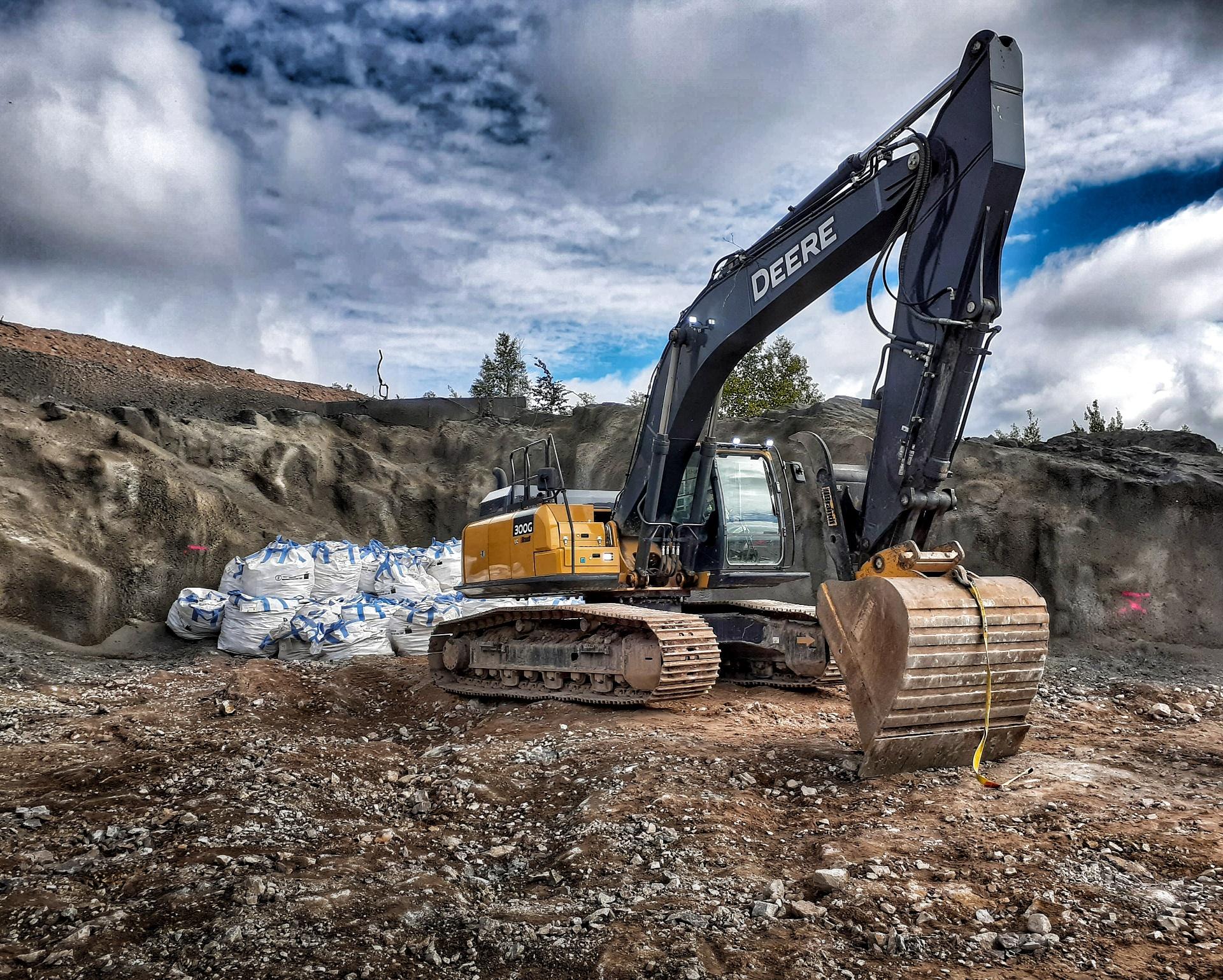 Excavator with contaminated materials behind