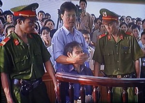 """In this photo taken from television shows a security man covers the mouth of the dissident Catholic priest Nguyen Van Ly, 60, after he twice yelled """"Down with the Communist Party"""" during his trial for spreading propaganda against the state at a local court in the central city of Hue, 30 March 2007. A Vietnamese court on 30 March sentenced dissident Catholic priest Nguyen Van Ly to eight years in jail for spreading propaganda against the state.    AFP PHOTO/HOANG DINH Nam      VIETNAM OUT NO INTERNET"""