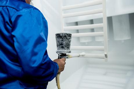 Worker performing powder coating of metal