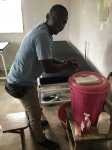 Dr. Sandy Gangha washing his hands at a hand washing station at the MOH clinic in Ngolahun. We have supplied the village with 80 stations like this to prevent the spread of COVID-19.