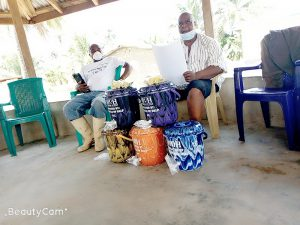 Paramount Chief Baion briefs the sub-chiefs on the distribution of the buckets.