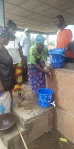 One of the female leaders demonstrating proper hand washing techniques to the village women.
