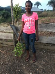 Jennifer Jabbie, Jusu's daughter proudly shows off a healthy young tree