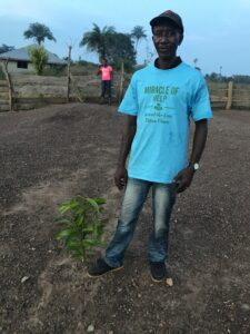 Jusu Jabbie, head man of the village stands over a young sapling