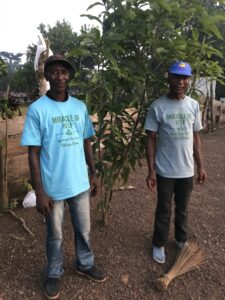 Jusu and MOH volunteer with one of our fastest growing trees