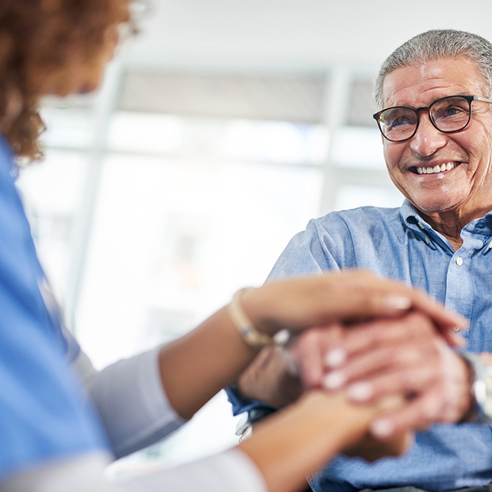 hot of a cheerful senior man holding hands with his nurse at a nursing home