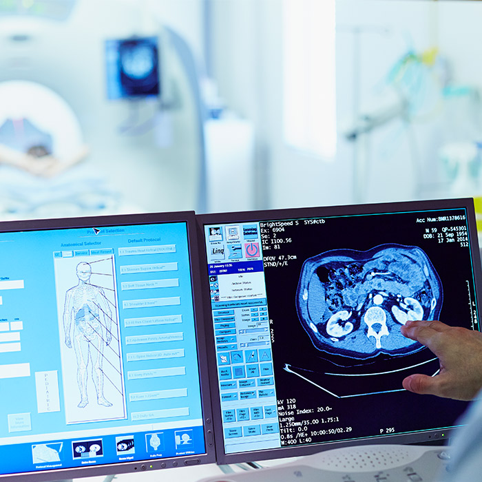 Male doctor running CT scan from control room at hospital