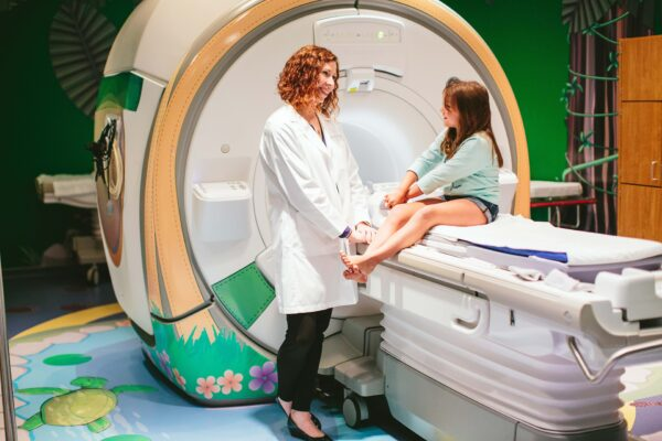 Girl sitting on MRI table